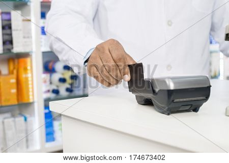 Midsection Of Chemist Swiping Credit Card On Reader