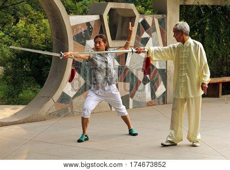 Yinchuan, China - Jul 7, 2011: Chinese Woman Doing Wushu Jian Form Under The Guidance Of A Mentor. T