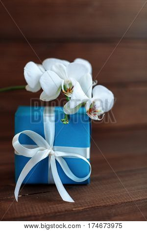 Gift and white orchid on a wooden background. The concept of celebration and a welcome card.
