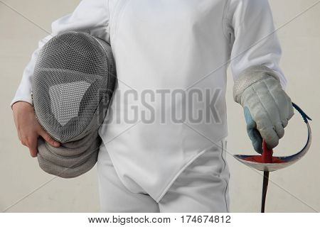 Female fencer hold epee and ferncer mask wearing white fencing costume isolated on white background
