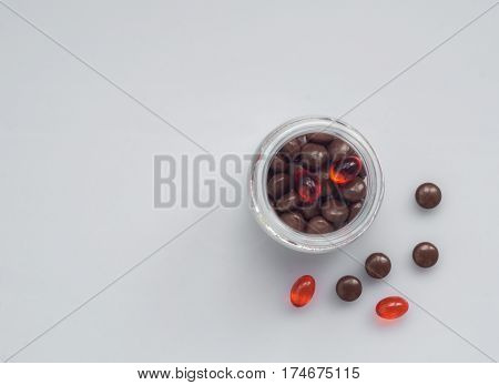 Different pills spill out of a glass jar on a light surface