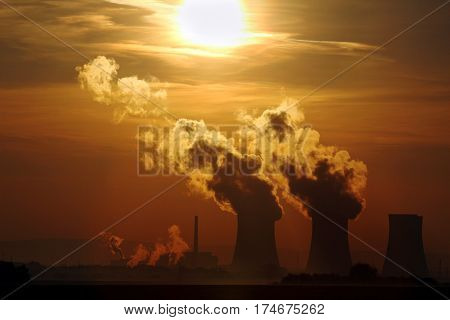 sun set over smoking nuclear power plant