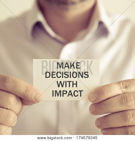 Businessman Holding Make Decisions With Impact Message Card