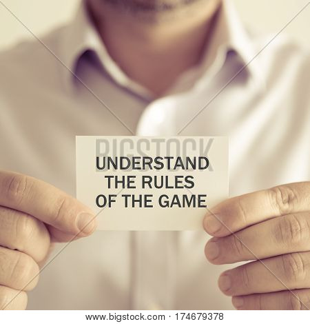 Businessman Holding Understand The Rules Of The Game Message Card
