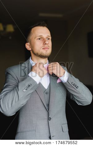 Elegant young fashion man dressing up for wedding celebration. Handsome groom dressed in modern gray suit white shirt and pink bow tie getting ready for event. Man adjusts his bow tie.