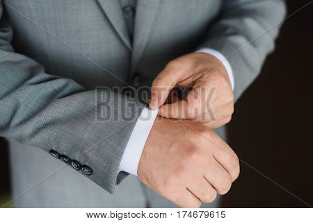 Elegant young fashion man dressing up for wedding celebration. Color close up image of male hands. Groom buttoning a shirt. Dark background.