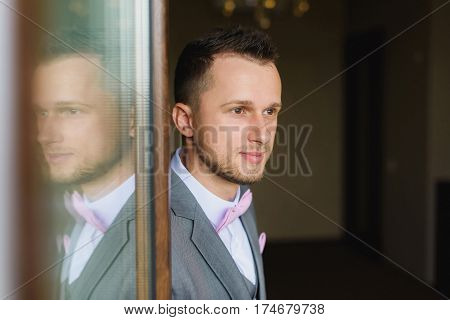 Portrait of young man wearing bow tie and suit. Groom silhouette reflected in the window. Elegant young fashion man dressing up for wedding celebration.