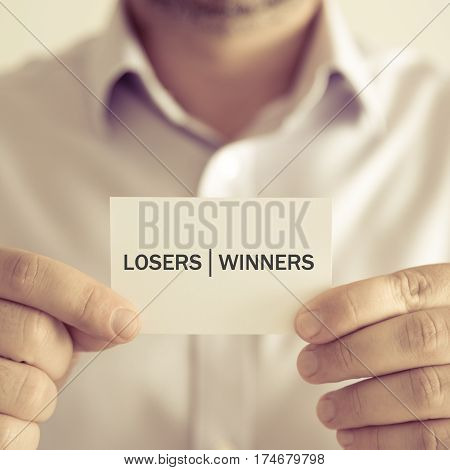 Businessman Holding Losers Winners Message Card