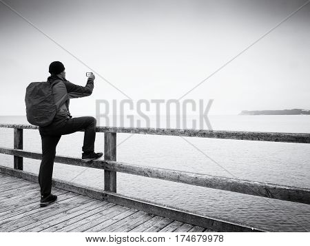 Alone tourist guide at sea pier handrail autumn misty morning.Man stay bellow old lamp. Depression dark atmosphere. Touristic mole wet wooden floor above sea.