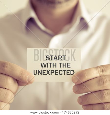 Businessman Holding Start With The Unexpected Message Card