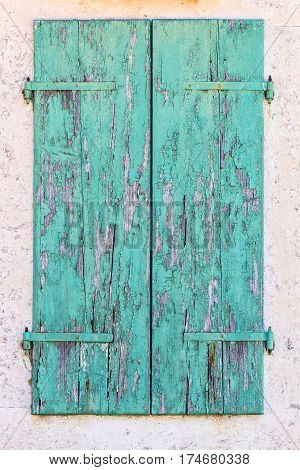 Old vintage retro wooden turquoise cracked paint window blinds shutter on white stone wall as historic architecture background
