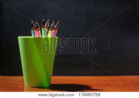 colored pens in glass on the background of blackboard
