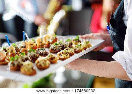 Waiter Carrying Plates With Meat Dish On Festive Event, Party Or Wedding Reception