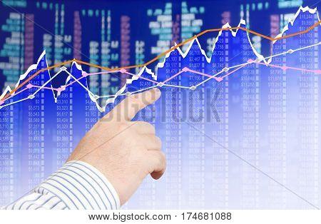 Businessman analyzing financial chart on screen .