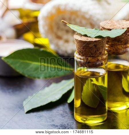 Healthy lifestyle concept. Natural bay laurel essential oil, essence in glass bottle with leaves, towels and candle on a rusty black table for beauty, spa, therapy