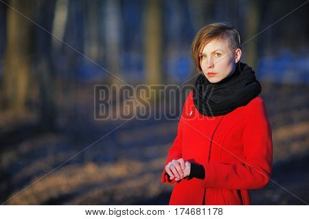 Portrait of young cute girl with a stylish haircut in a red coat and black scarf at the neck posing in the bright sun on a blurred background of trees in the Park