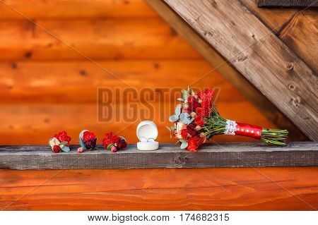 Two wedding rings in white box lying near bouquet with red roses and three flower buttonholes on wooden background