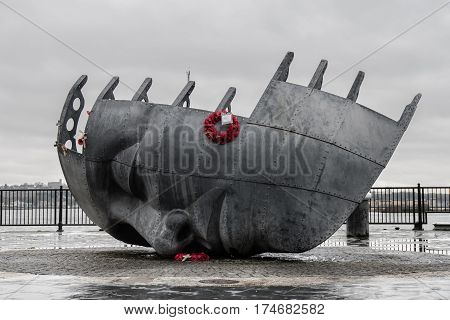 Cardiff Wales UK - February 25 2017: Merchant Seafarers' War Memorial with poppies. Public art by Brian Fell in memory of sailors from the ports of Barry Penarth and Cardiff killed in war