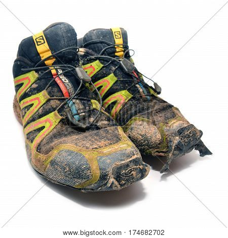Caransebes Romania - January 27 2016: A pair of worn ripped and dirty Salomon trail running shoes over white background. Shot taken on January 27th 2016.