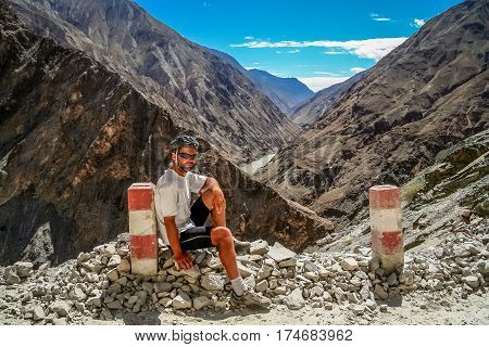 tired male cyclist resting on a pile of rocks while on a cycle touring trip in yunnan province, china