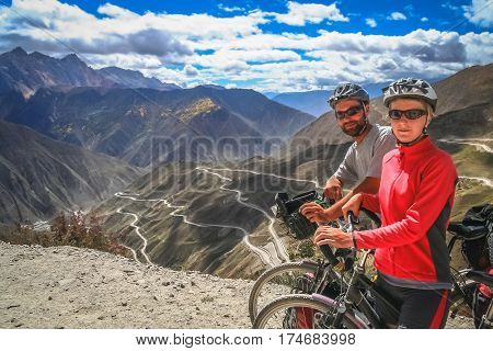 Couple posing for a photo on top of a mountain pass while on a cycle touring trip in Yunnan Province, China