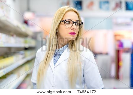 Blonde Pharmacist Chemist Woman Standing In Pharmacy Drugstore, Smiling And Wearing Glasses. Blonde