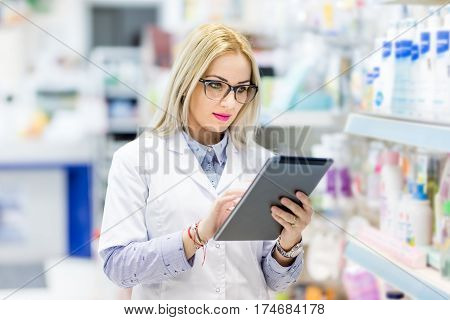 Pharmacy Details - Blonde Doctor In White Uniform Using Tablet And Technology In Pharmaceutical Or M