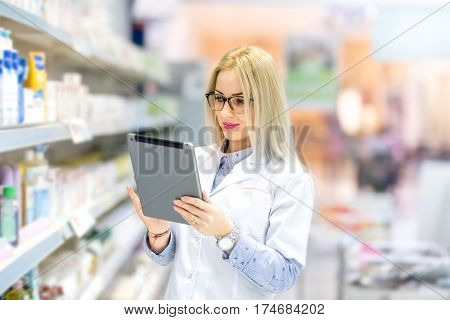 Portrait Of Pharmacist Chemist Woman Standing In Pharmacy Drugstore, Smiling And Using Tablet.