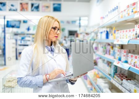 Sexy Blonde Pharmacist In Medical Field Using Laptop And Tablet Technology For Posting Online Drug A