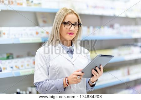 Cute Blonde Doctor In White Uniform Using Tablet And Technology In Pharmaceutical Or Medical Field