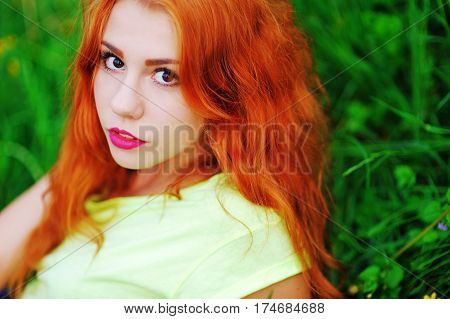 Portrait of a cute red-haired girl with beautiful brown eyes resting on a green lawn in a Park closeup.