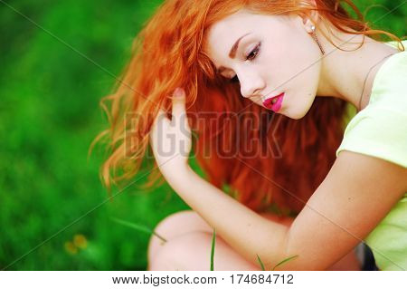 Portrait of a beautiful red-haired girl thoughtfully sitting on green lawn in Park side view closeup.