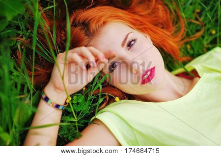Young beautiful pensive red-haired woman in a green blouse relaxes in the Park lying on green grass close-up
