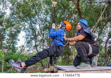 Labuan,Malaysia-Feb 12,2017:Happy muslim girls enjoying play on a flying fox in Labuan,Malaysia.There will be more ziplines in Malaysia,especially when there have so much natural resources & rainforest.