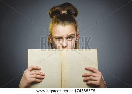 wondering girl with book. Closeup Portrait of handsome teen on grey background. studies concept.