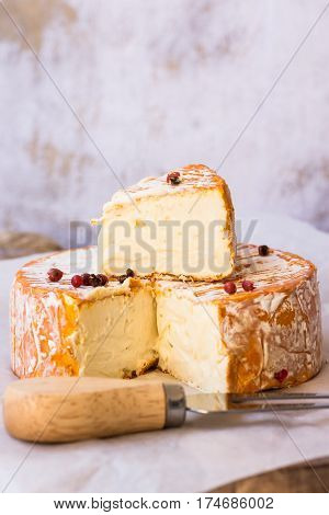 French German soft cheese with orange washed-rind fork red pepper corns cutting board concrete wall background