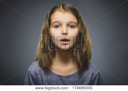 wondering girl. Closeup Portrait of handsome child in casual shirt on grey background.