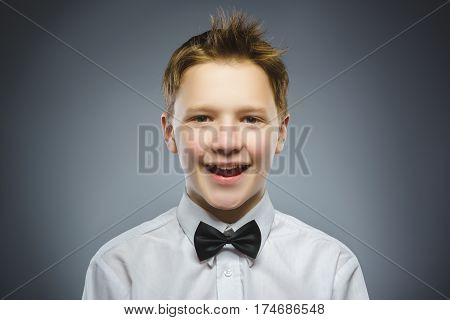 Happy boy. Closeup Portrait of handsome boy smiling isolated on grey background.