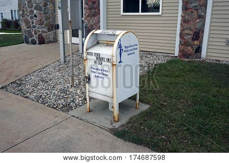 MANCELONA, MICHIGAN / UNITED STATES - NOVEMBER 27, 2016: One may deposit payments for one's water and sewer bill into a white box in front of the Mancelona Village Offices building on State Street in downtown Mancelona.
