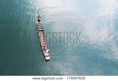 SANGKLABURI KANCHANABURI THAILAND - March 1 2017 : A fisherman rides long tail boat across Songkhalia river Sangklaburi Kanchanaburi Thailand.