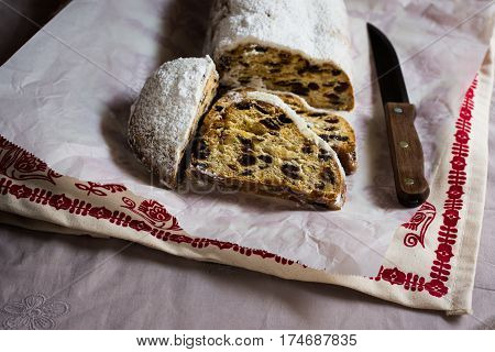 Sliced German Christmas stollen with knife on waxed paper over ornamented linen towel minimalistic style cozy atmosphere