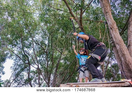 Labuan,Malaysia-Feb 12,2017:Happy kid ready to play on a flying fox in Labuan,Malaysia.There will be more ziplines in Malaysia,especially when there have so much natural resources & rainforest.