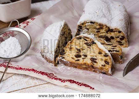 German sliced Christmas stollen on waxed paper over kitchen towel sieve with sugar powder ingredients wood kitchen table cozy