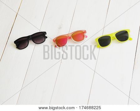 Baby's colorful sunglasses on a wooden background