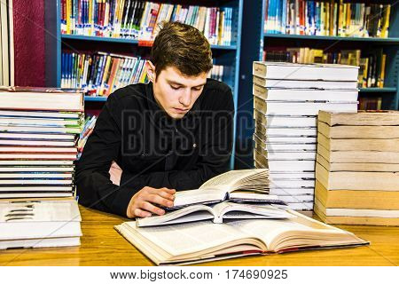 Library education concept. University students studying with books in library, Young student sitting at table with books and reading, Schoolboy in the library. Library, teenager reading a book.