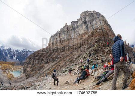 Lake Louise Canada - September 17 2016: Hikers rest atop Sentinel Pass in the Larch Valley near Lake Louise in Banff National Park Alberta with Pinnacle Mountain and Valley of Ten Peaks in the background.