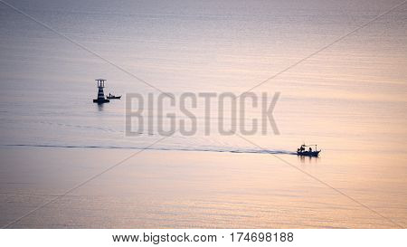 aerial view silhouette of fishery boat sail on calm sea with lighthouse background at sunrise