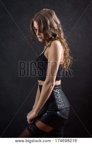 luxury young woman undressing on black background