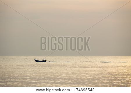 silhouette minimalist image of single local fishery boat sail on calm sea in sunrise with copy space