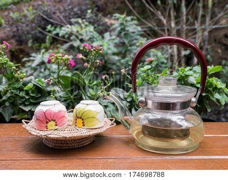 Cup of tea and teakettle on bar at garden Chiangmai Thailand